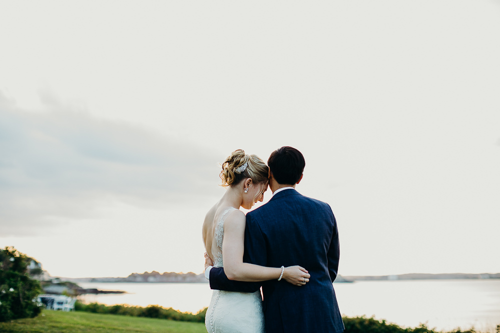 A wedding photo of a couple watching the sunset at their New England coastal wedding in Nahant.