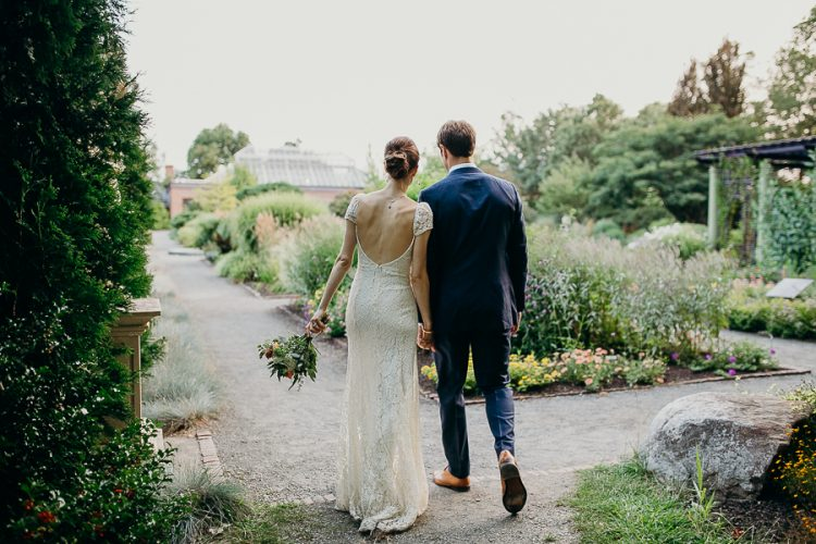 A wedding photo of a couple walking in the garden at their Tower Hill wedding in Massachusetts.